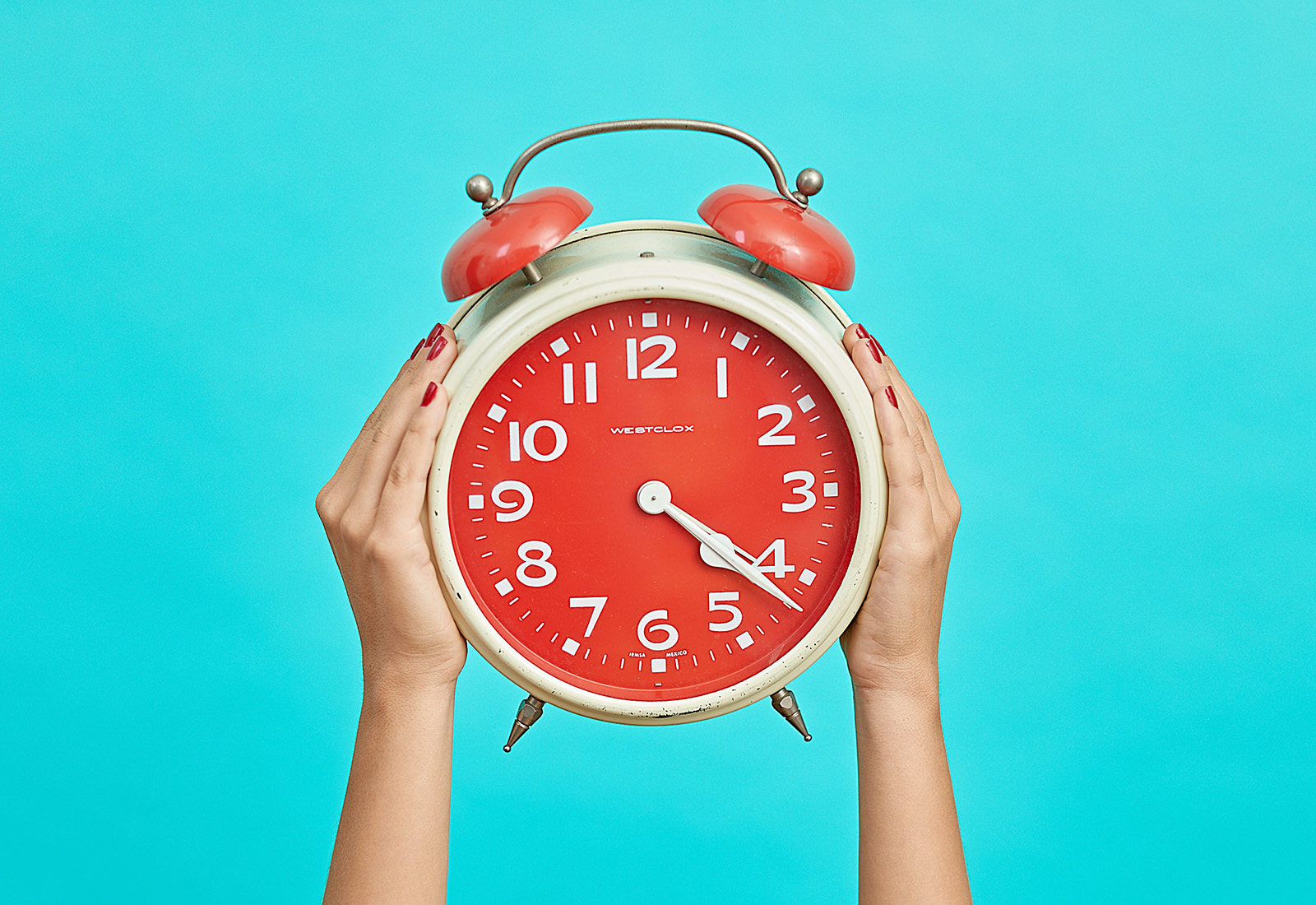 red westclox clock against turquoise background