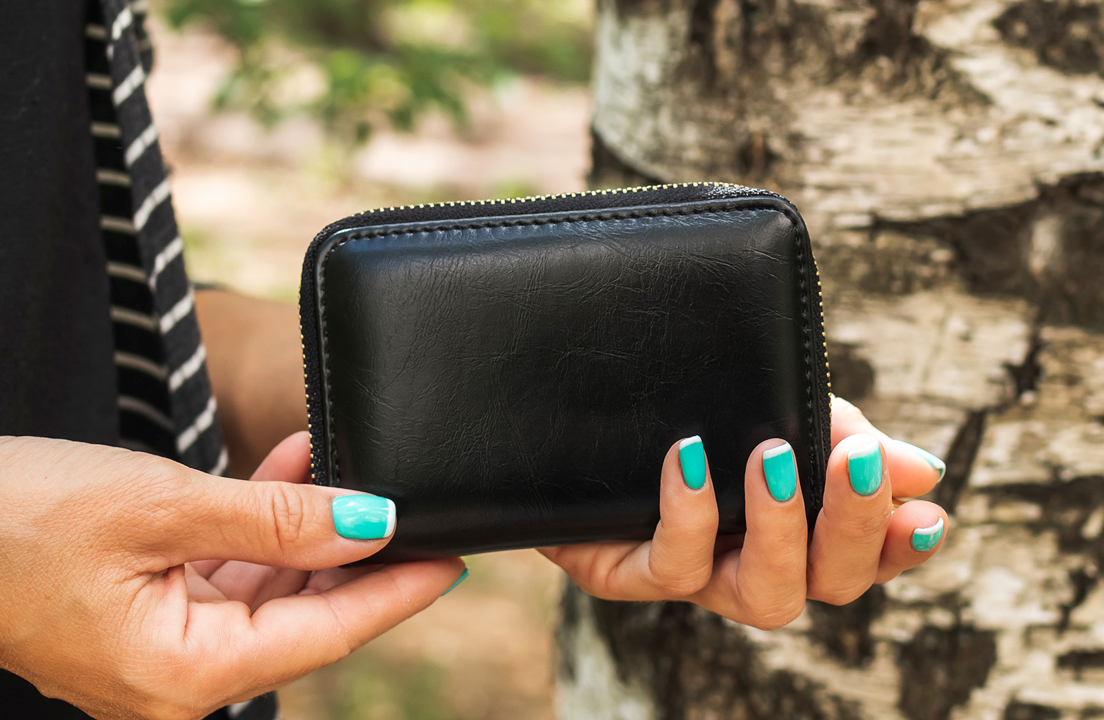 Black wallet being held by painted nails