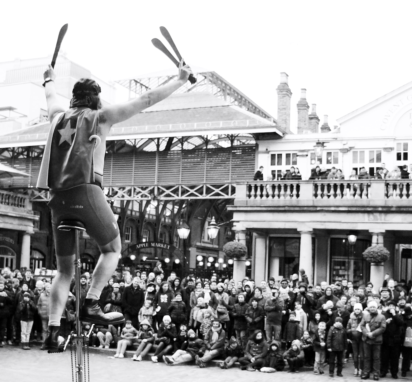 Black and white image of juggler on a unicycle in front of a crowd