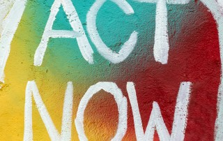 Sign of colorful mural with white text that says Act Now